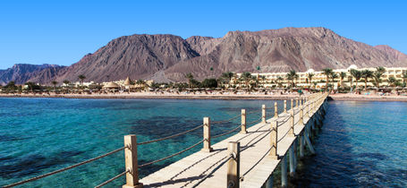 Pier over Red Sea reef with beach resort and mountain backdrop in Dahab Egypt.