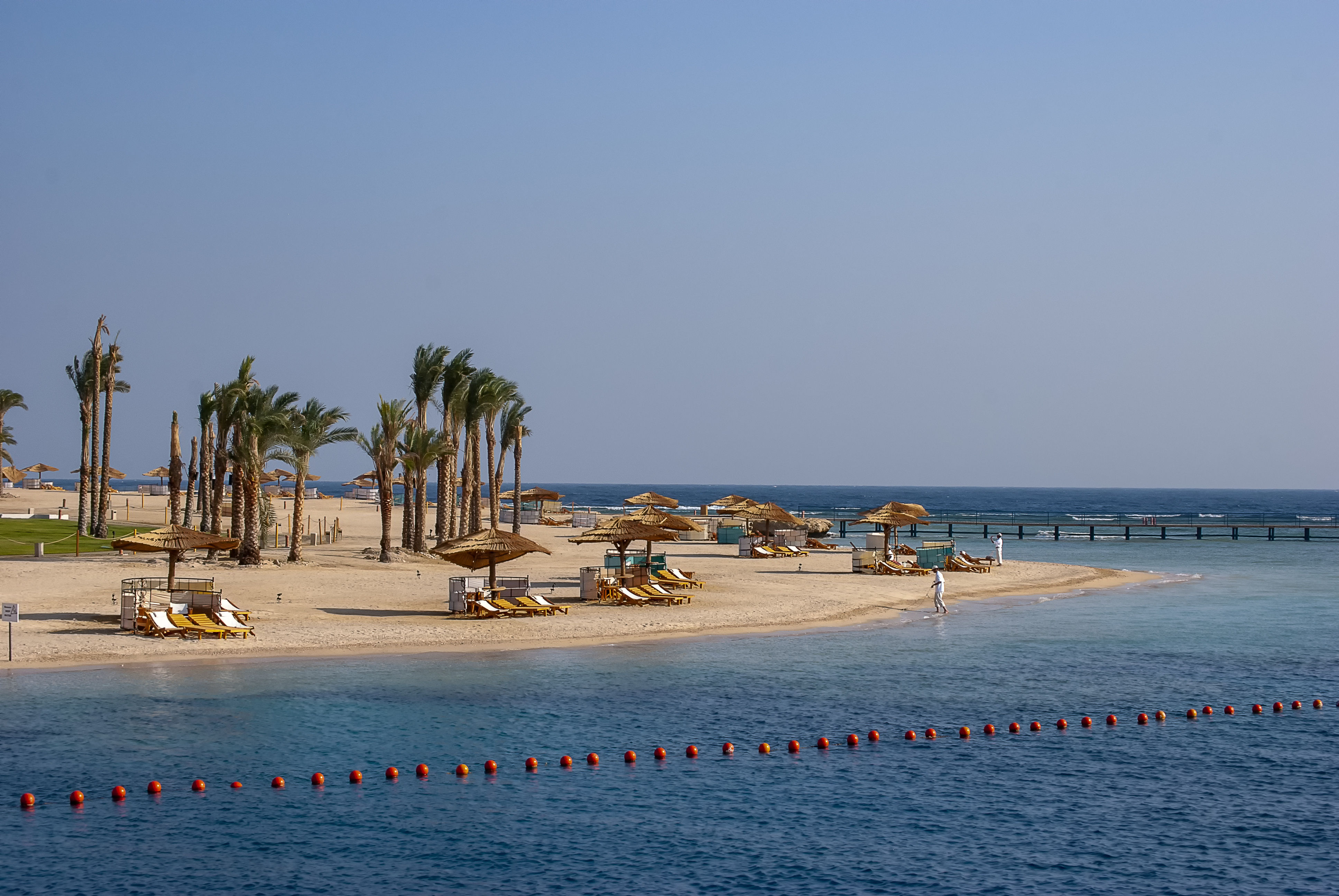 Palm trees and beach umbrellas on Red Sea holiday resort of Port Ghalib in Egypt.