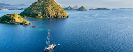 Sailing boat on blue sea with many small islands in Komodo national park in Indonesia.