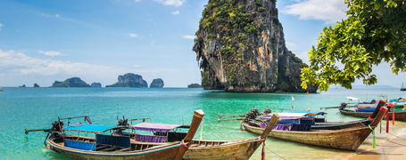 Long tail boats moored on a golden sand beach with limestone islands in the tropical Phang Nga Bay in Thailand.