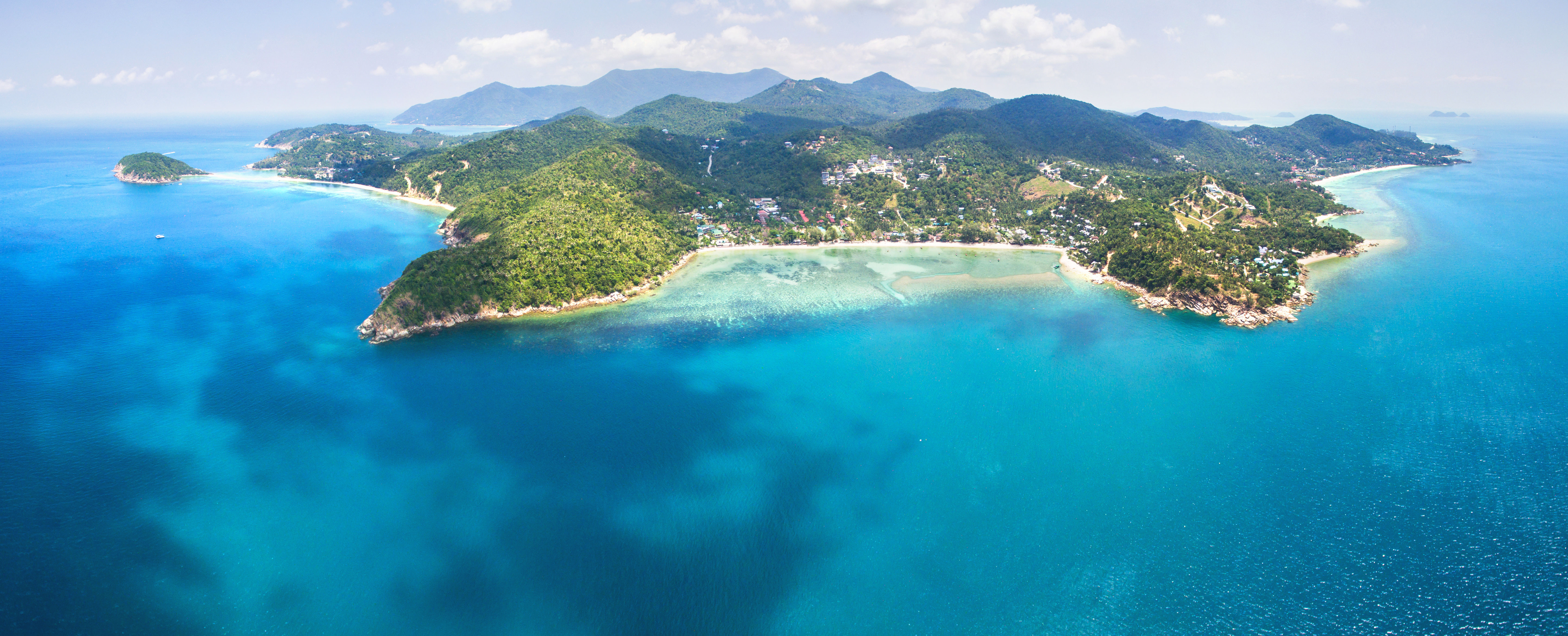 Aerial panoramic view of tropical island of Koh Phangan, Thailand, surrounded by reefs and white sand bays.