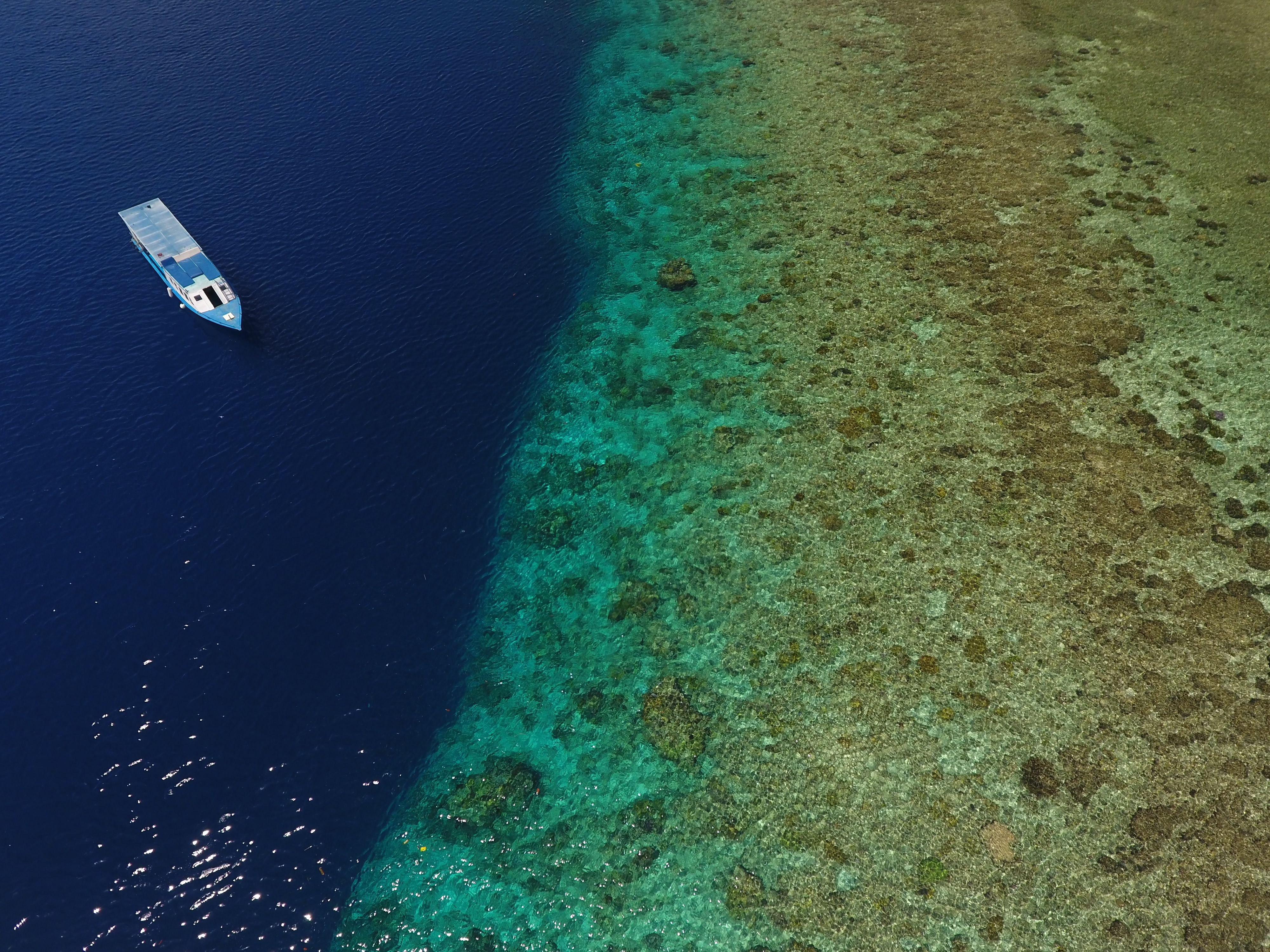 Scuba diving boat next to coral reef on tropical sea in Manado Indonesia.