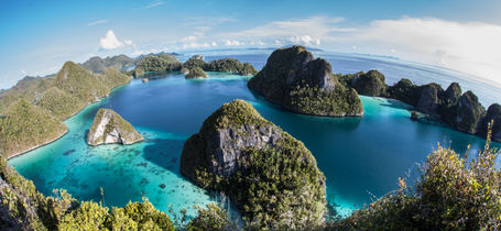 Aerial view of Indonesian archipelago, Raja Ampat jungle covered Islands in tropical seas.