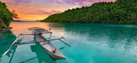 Traditional Indonesian boat floating on blue green lagoon in the Togean Islands, Sulawesi at sunset.