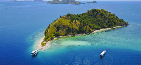 Aerial view of Flores with tour boat, turquoise and blue sea in Indonesia.