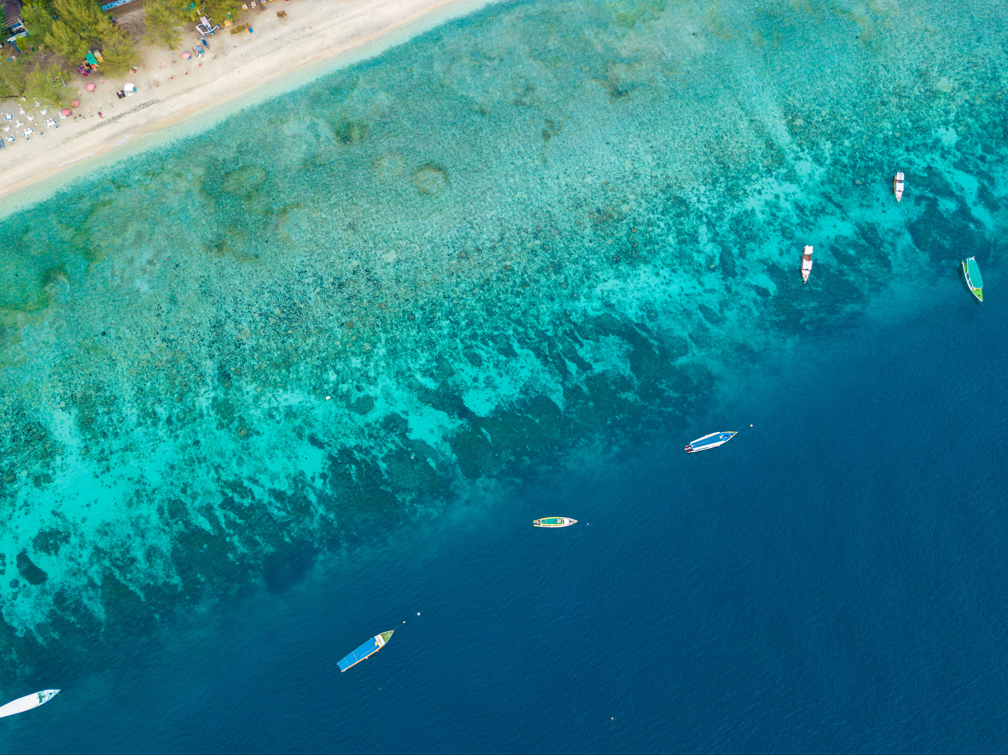 Aerial view of Gili Island coastline with boats, white sand and turquoise waters, West Nusa Tenggara, Indonesia.