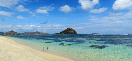 White sand tropical beach with shallow reef and blue skies in Moyo Indonesia.