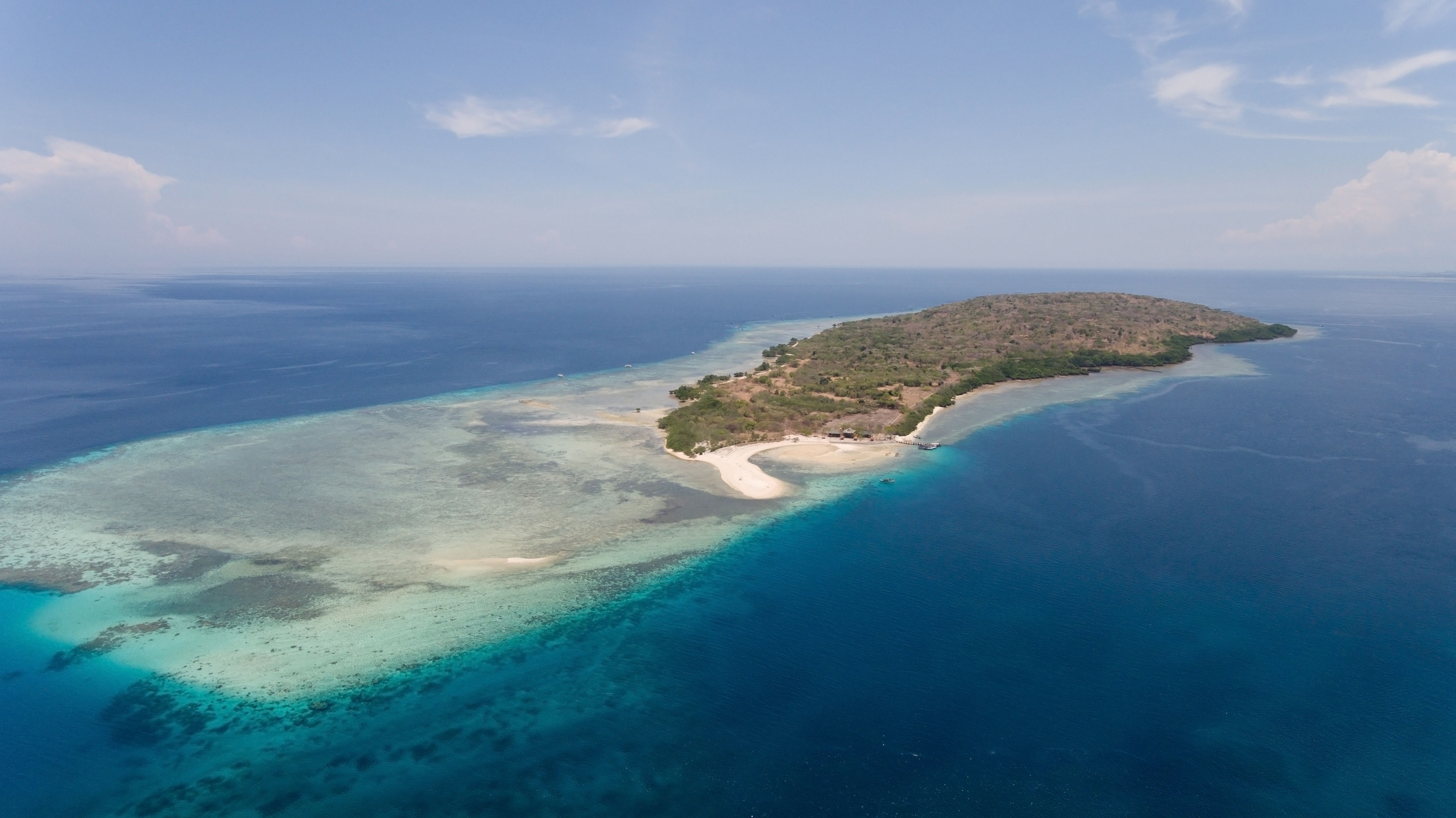 Aerial view tropical island Menjanga with white sand beach, coral reef, atoll and blue waters.