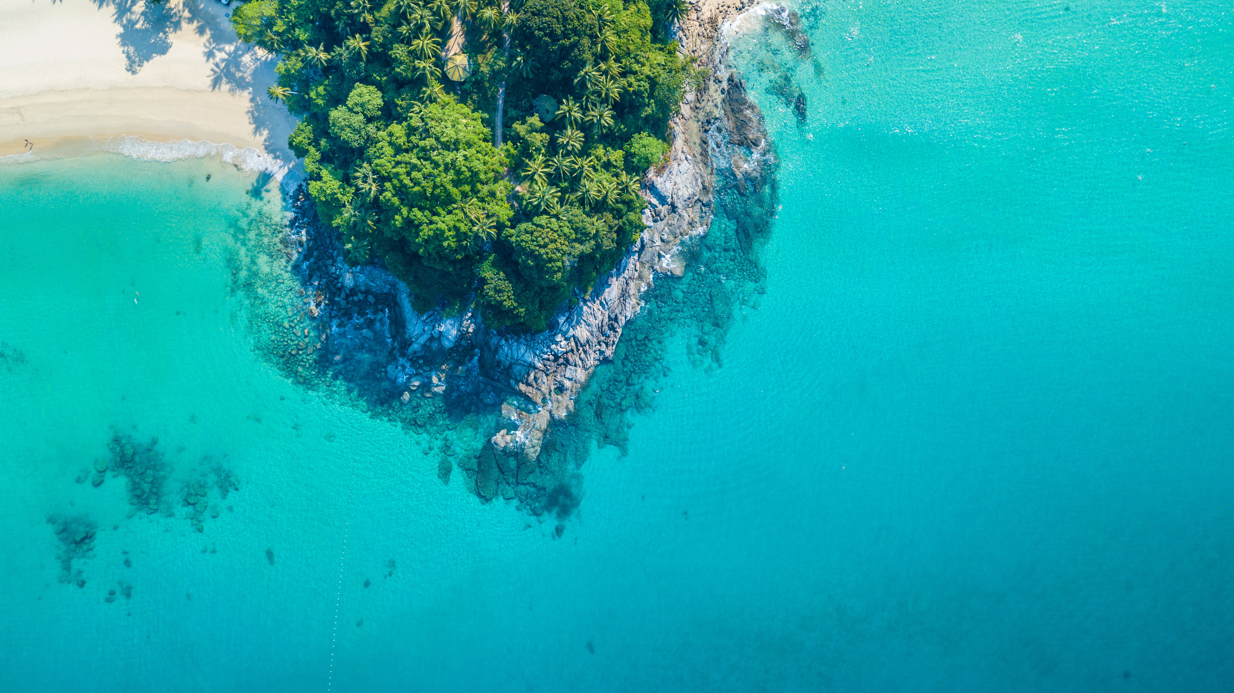 Tropical island outcrop with rocks and palm trees, surrounded by turquoise waters in South East Asia.