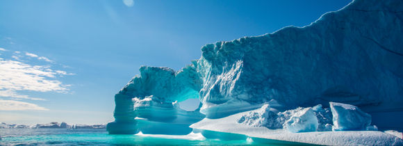 Beautiful icebergs on a sunny day with blue sky and green water in the Arctic Circle.