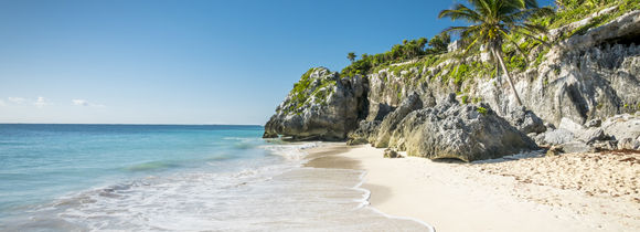 White sand tropical beach with palm trees and rocks in Tulum, Mexico.