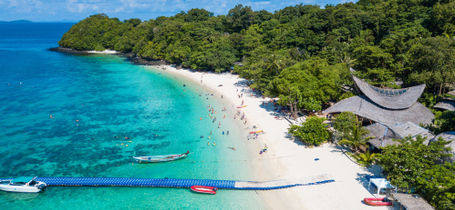Aerial view of tropical island beach with clear water, jetty and white sand beaches of Koh Hey, Phuket.