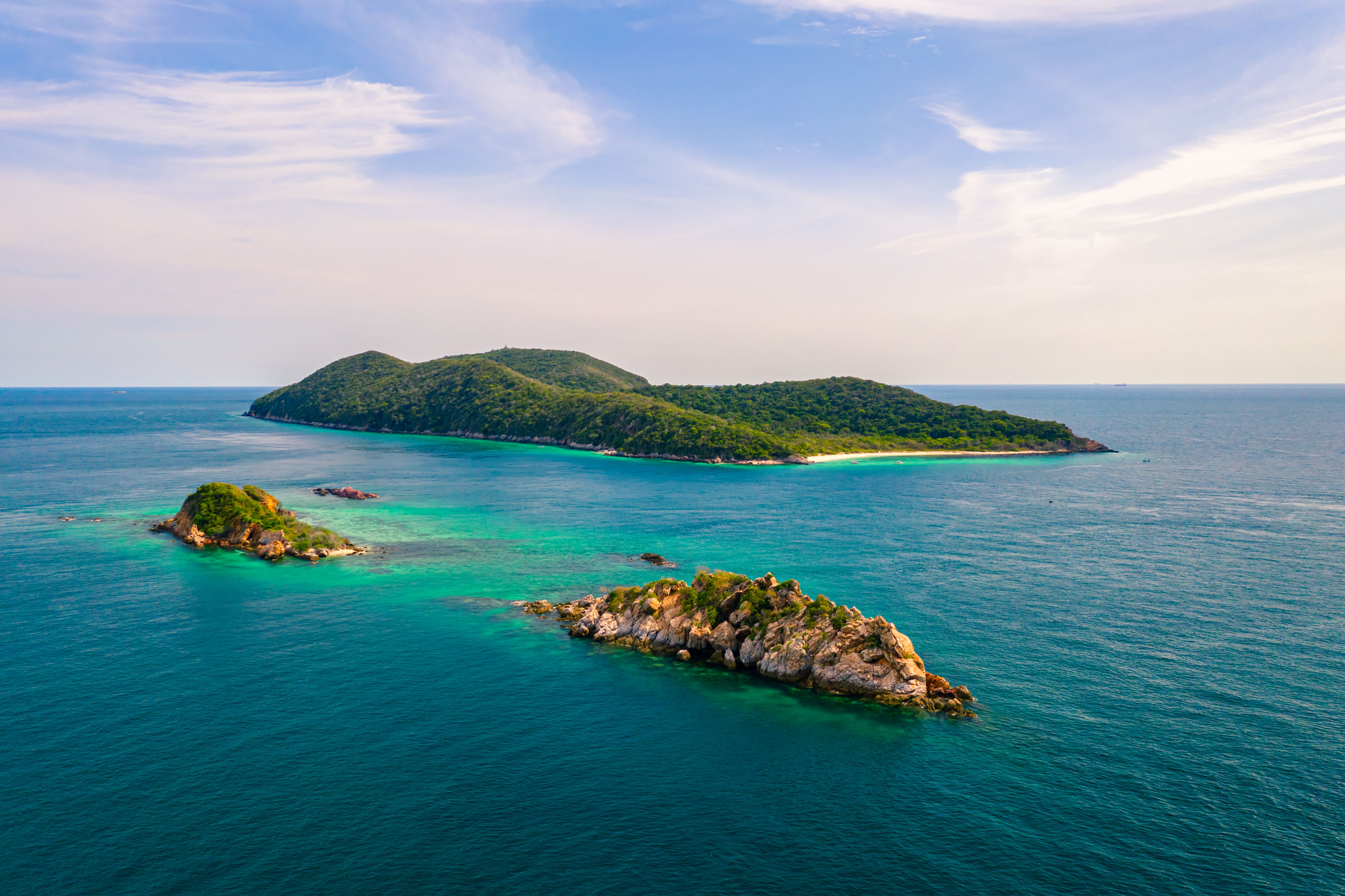 Aerial view of three small islands covered in green trees surrounded by blue waters in Chonburi, Thailand.