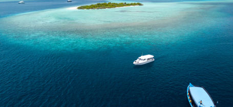 Aerial view of scuba diving boats near tropical islands in Baa Atoll Maldives.