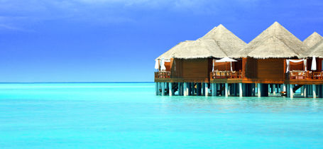 Wooden bungalows over turquoise waters of Kaafu Atoll in the Maldives.