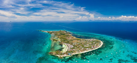 Drone aerial view of Malapascua Island surrounded by coral reefs in the Philippines.