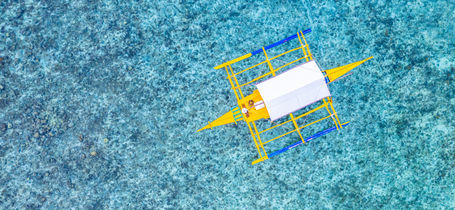 Aerial view of Filipino Paraw boat floating on tropical waters of Moalboal, Cebu, Philippines.