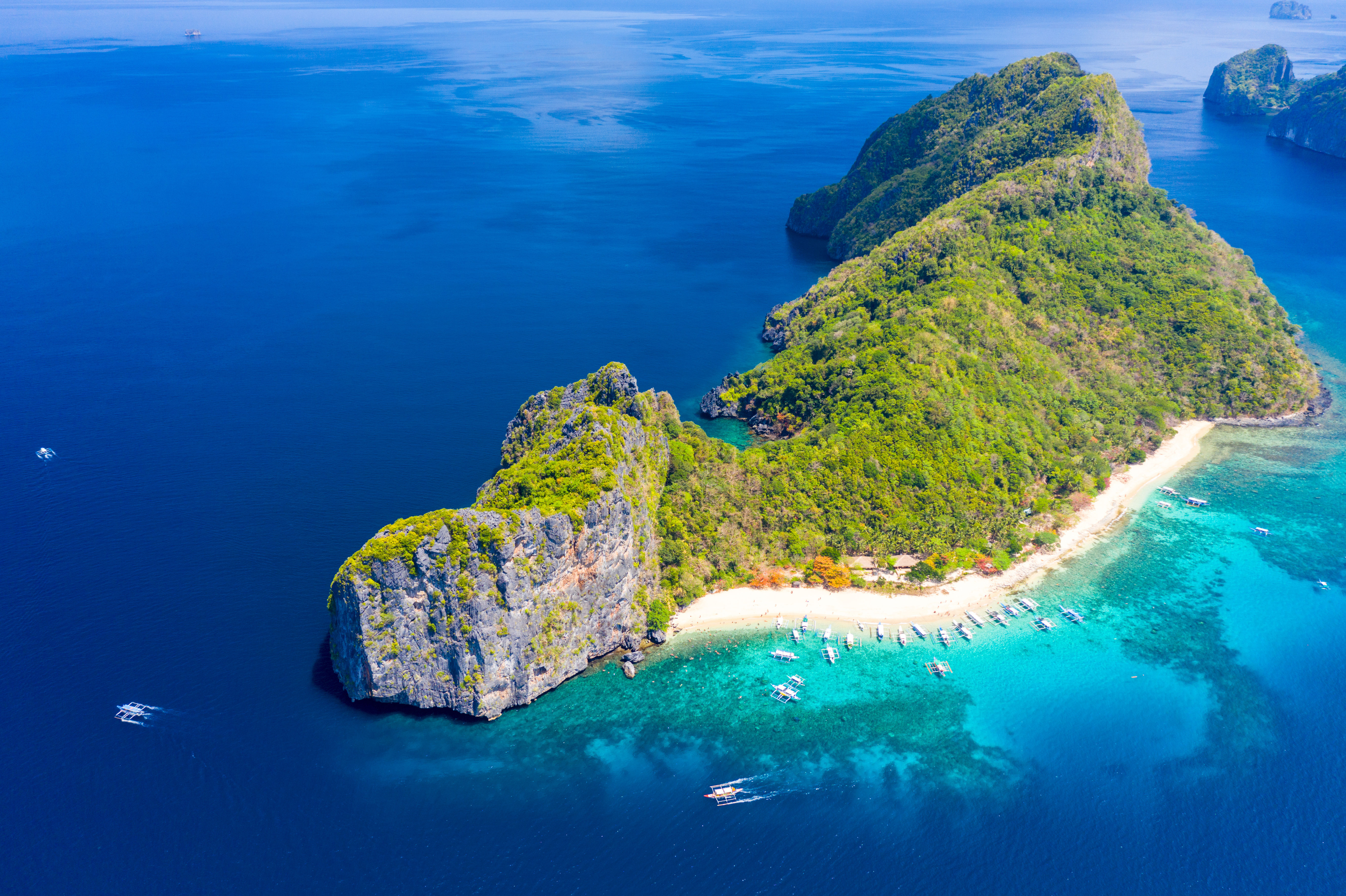 Aerial drone view of a tropical white sand island in El Nido, Palawan, Philippines with limestone cliffs and shallow reefs.
