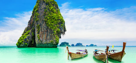 Three traditional longtail boats on turquoise water next to limestone rock in Krabi.