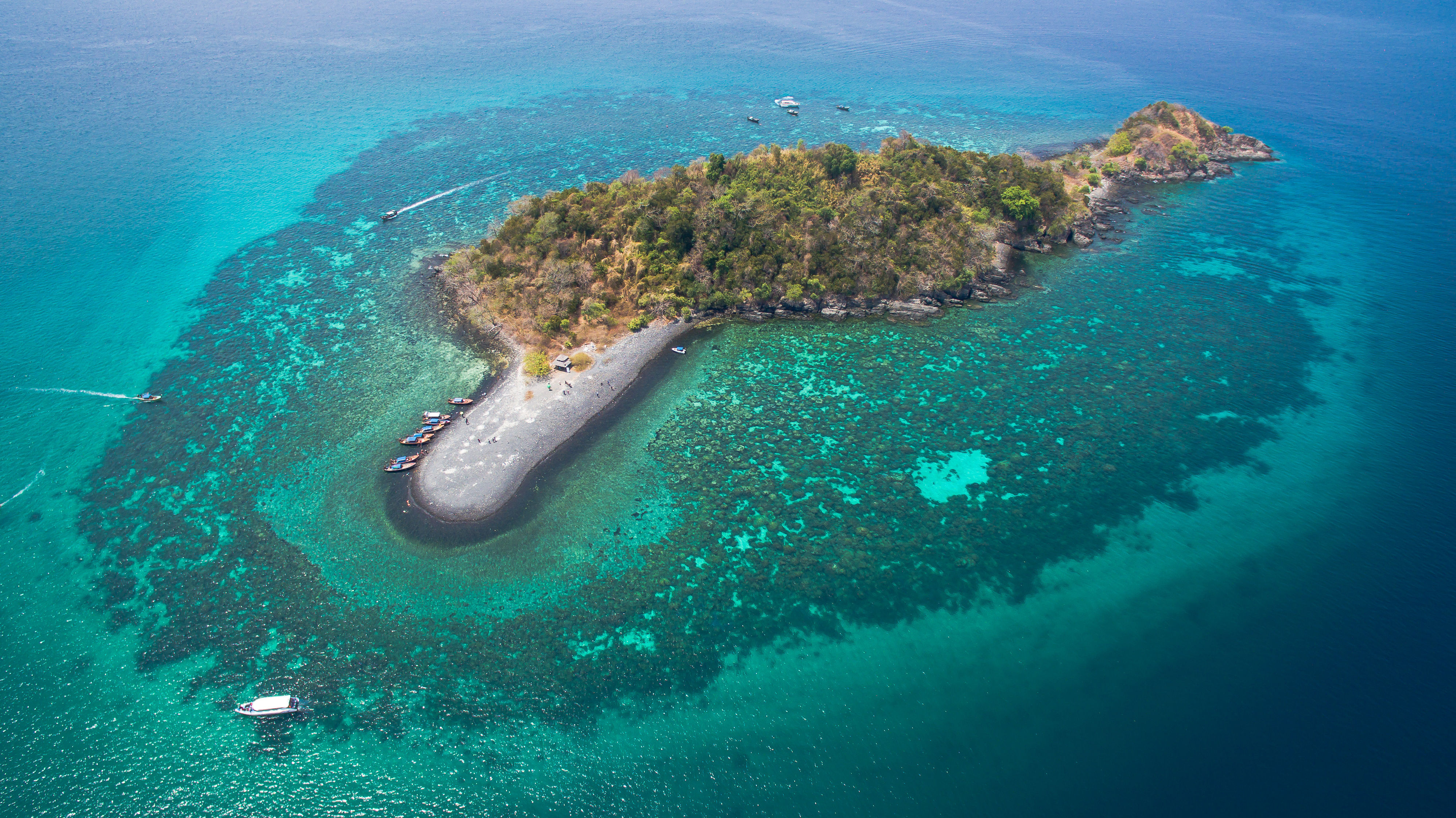Aerial view of tropical island surrounded by shallow reef and boats in Satun, Thailand.