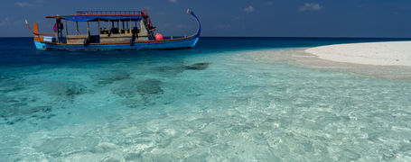 Traditional Maldivian Dhoni next to white sand island in Central Atoll on tropical turquoise waters.