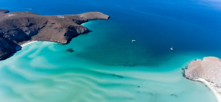 Aerial view of rocky headland, boats and blue waters of Balandra beach, Baja California Sur, Mexico.