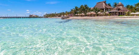 Tropical beach and resort, surrounded by shallow crystal clear waters and wooden jetty in Quintana Roo, Mexico.