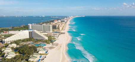 Aerial panorama view of Cancun beach strip with hotels and tropical waters.