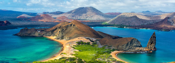 Aerial panorama view from Bartolome Island in Galapagos with rocky hills, green grass and blue waters. South America