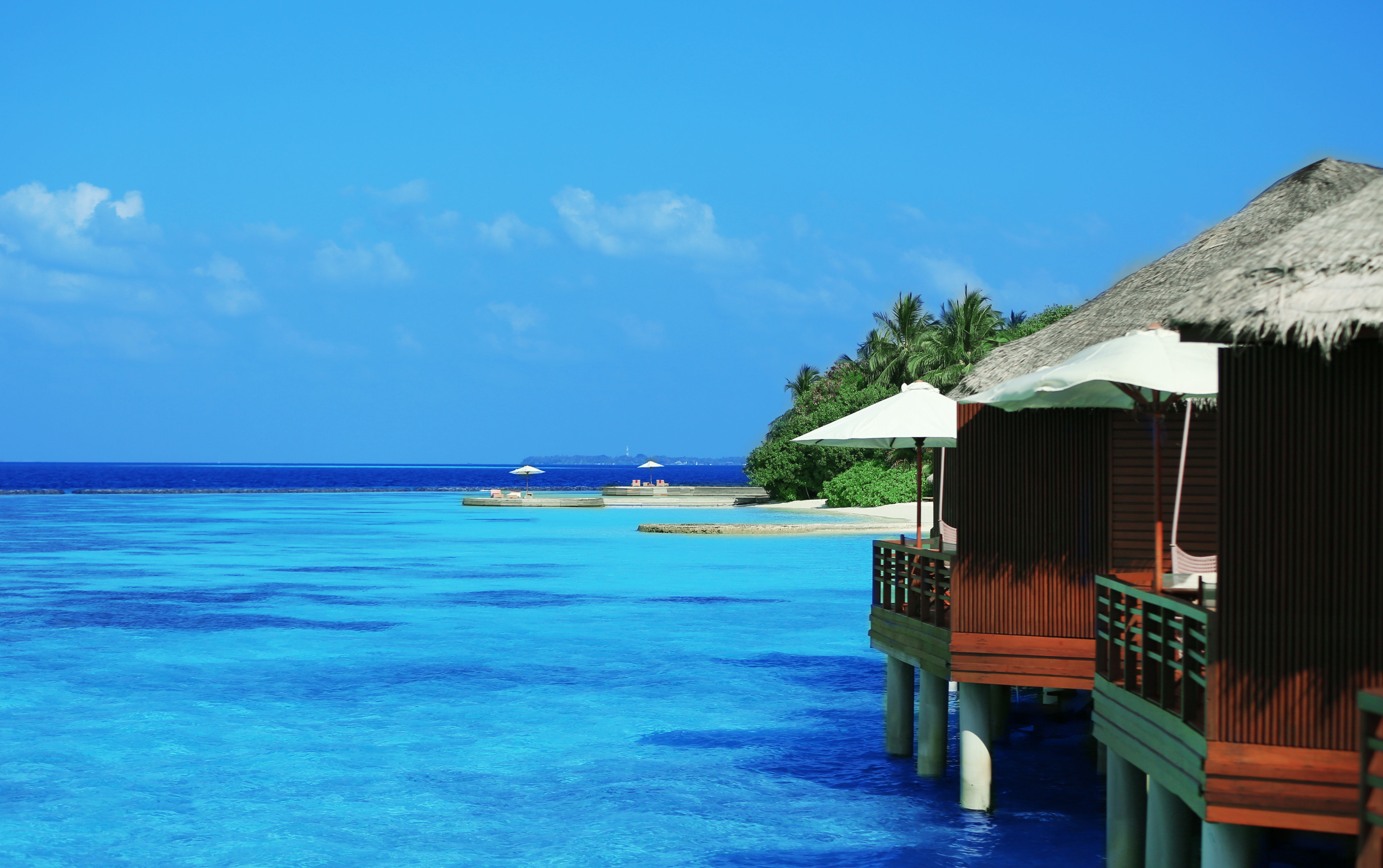 Water villas on crystal clear turquoise ocean in South Central Asia with blue sky background.