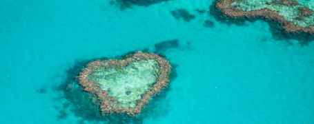 Aerial view of Heart Reef surrounded by crystal clear turquoise waters in the Great Barrier Reef in Australia.