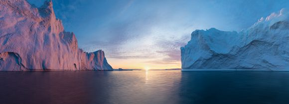 Midnight sun rising in between two icebergs in Antarctica.