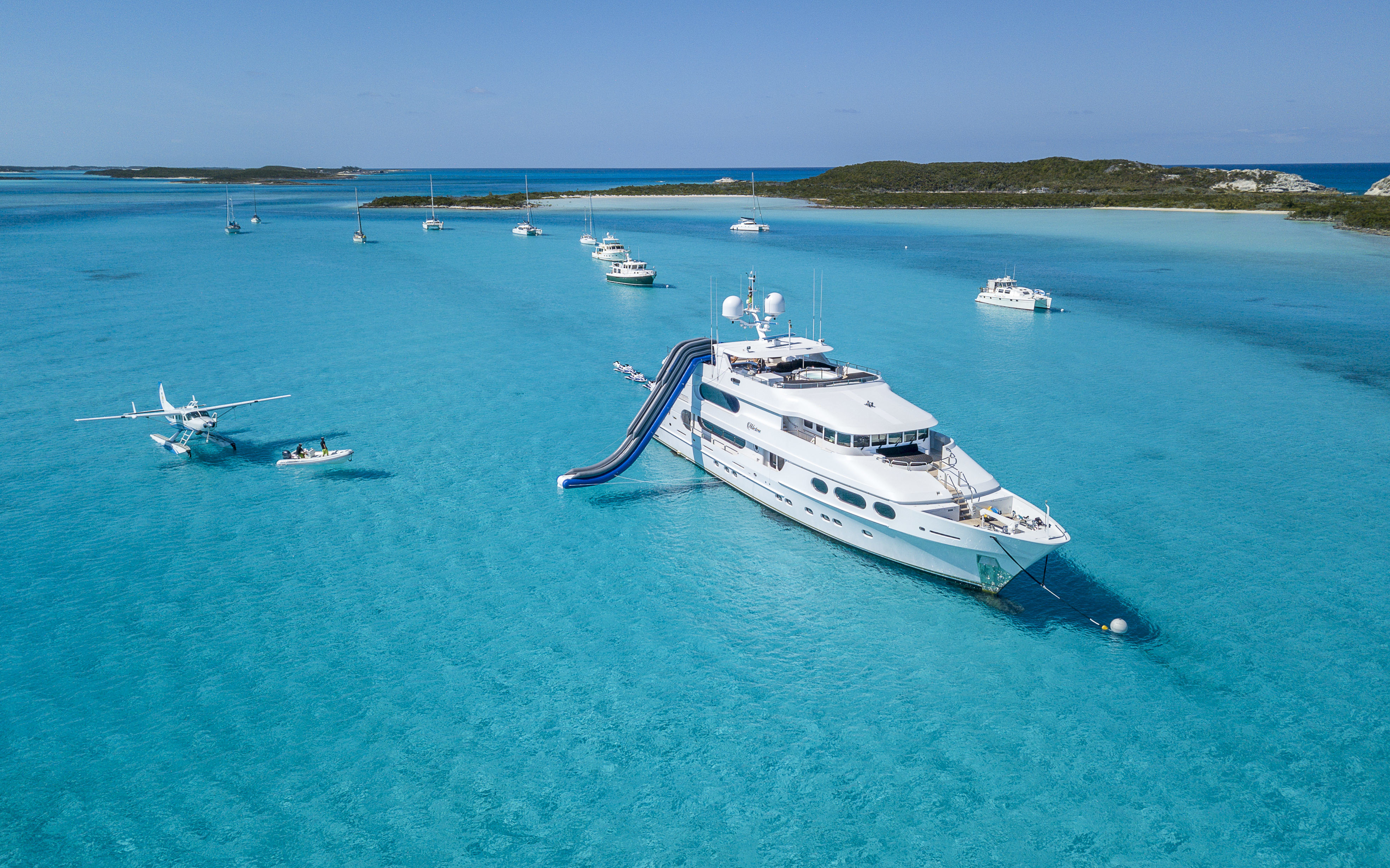 White yachts and sea plane on azure blue waters near islands in the Bahamas.