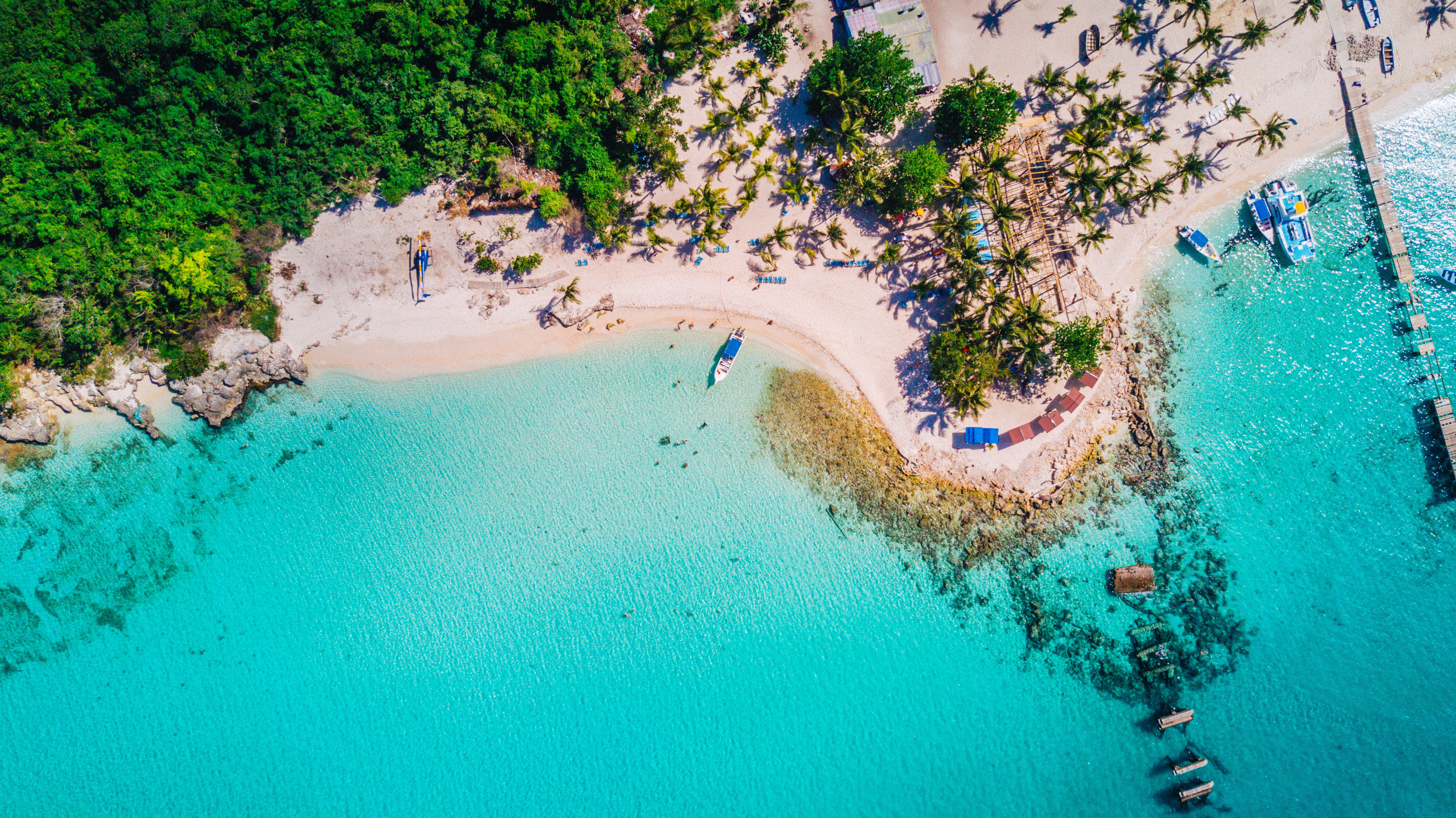 Aerial drone view of reef, trees and beach in a tropical landscape with boats in Dominican Republic.