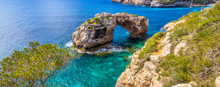 Natural rock arch out on turquoise waters and blue skies in Spain.