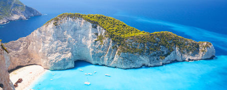 Beautiful white cliff bay with white beach and aqua blue water on a Greek island.