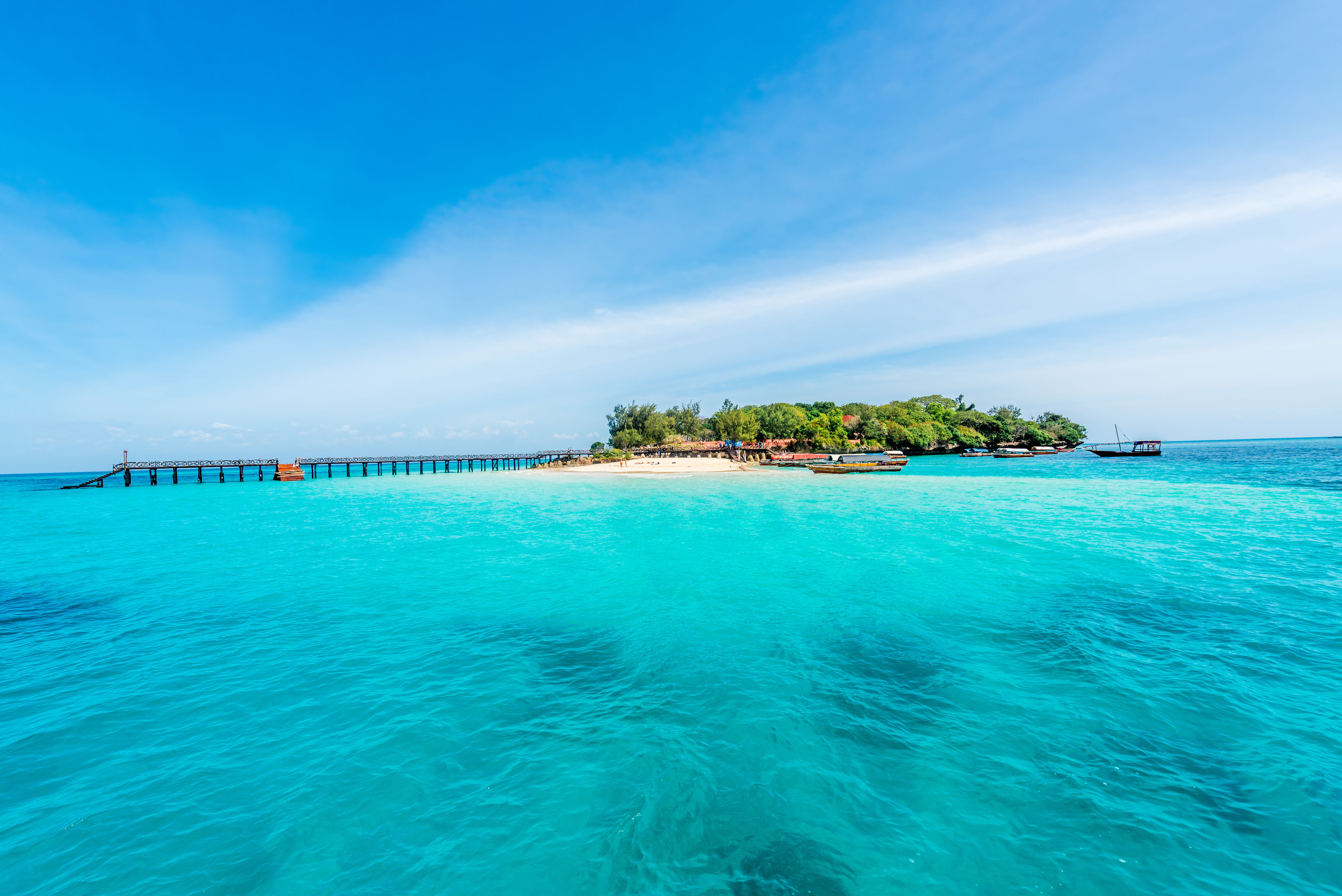 Small tropical island with wooden jetty, surrounded by turquoise waters and clear blue skies off Madagascar.