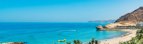 Beautiful golden sand beach with green trees, mountains and blue sea and sky in Oman.