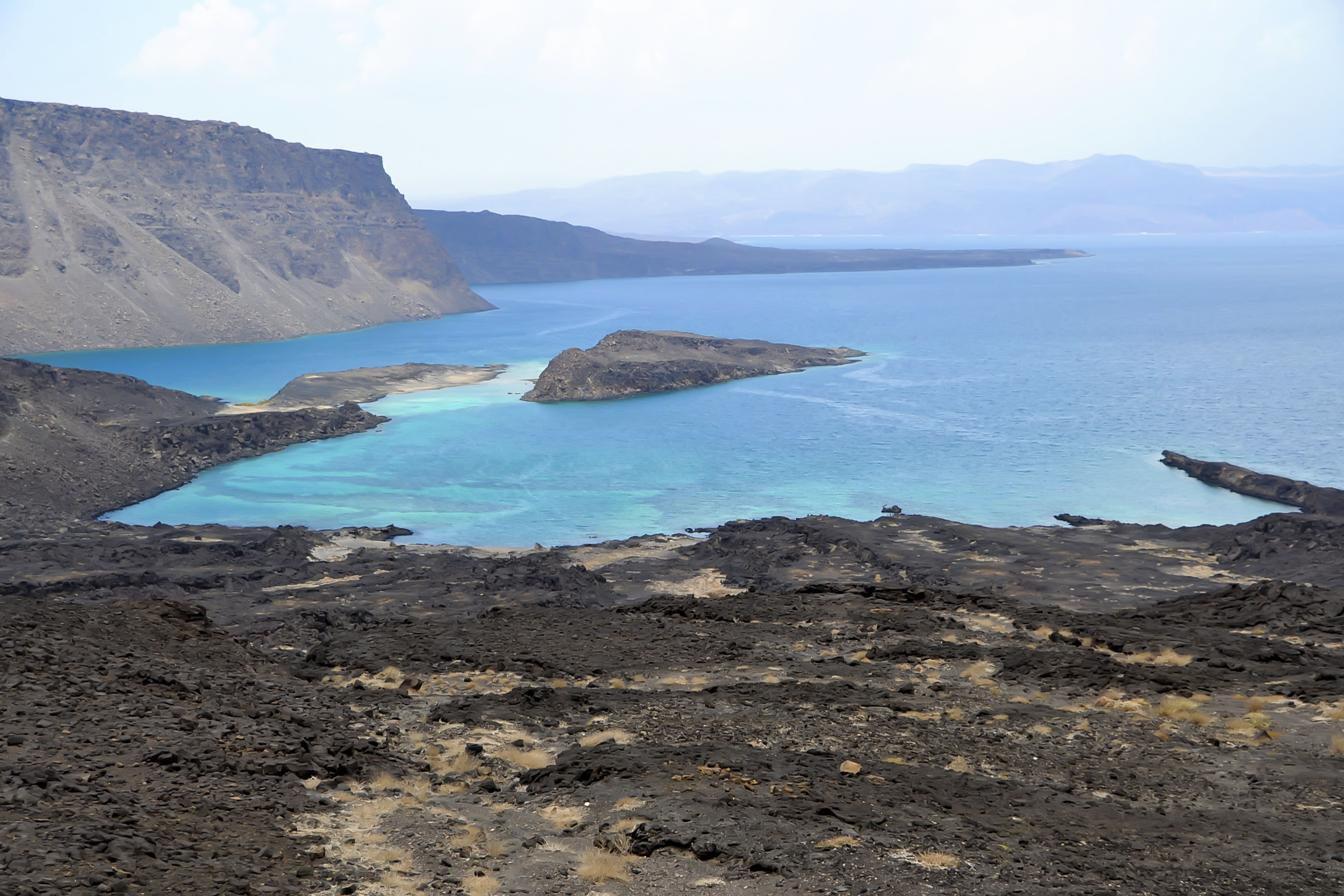 Panorama view of dark sand beach in Djibouti, with blue waters, cliffs and clear skies.