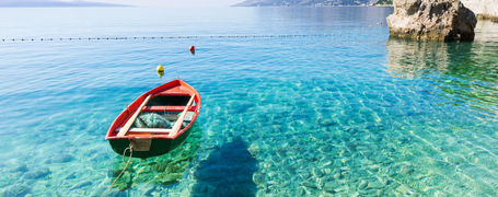 Small red boat on crystal clear waters in beautiful bay in Croatia.
