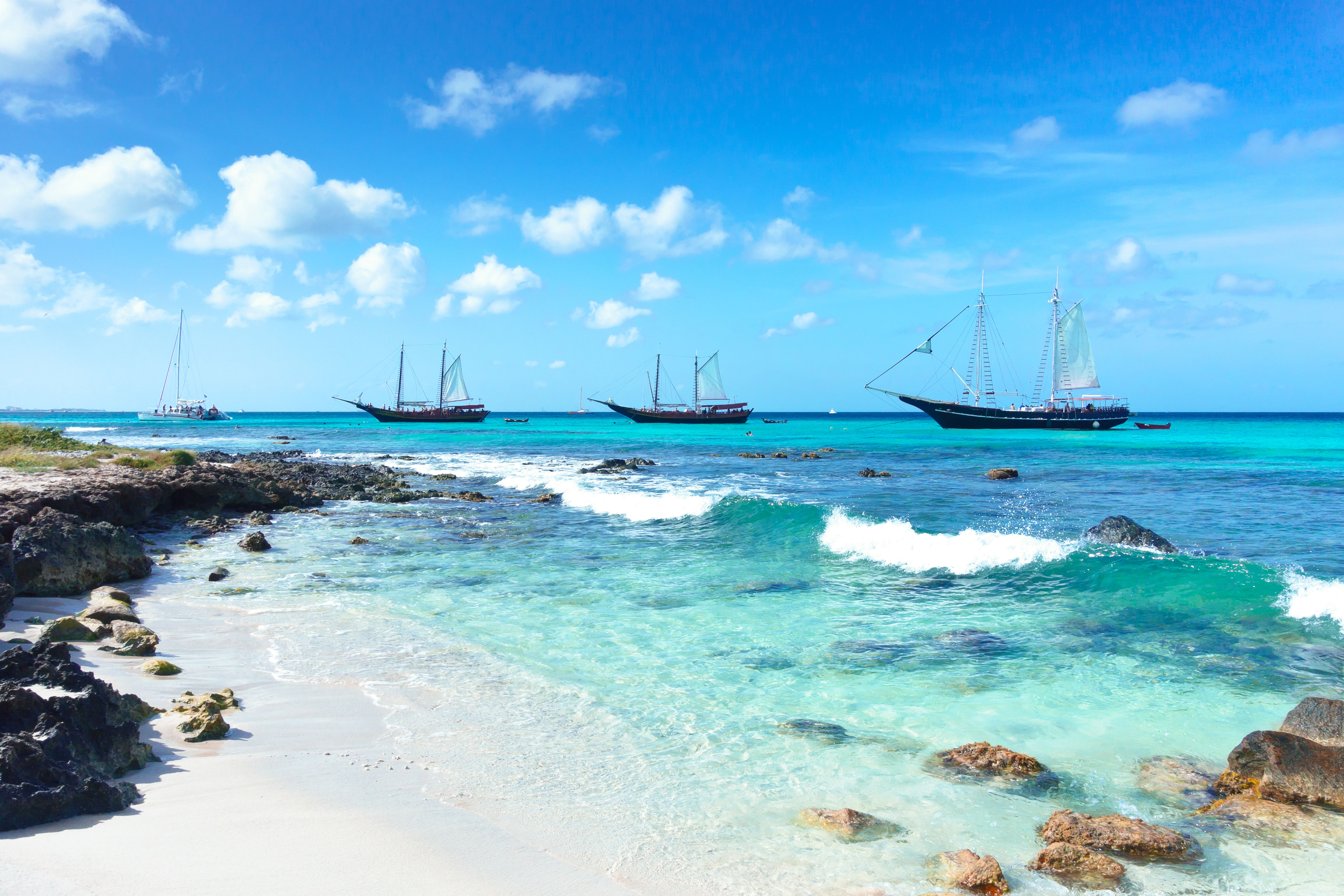 Sail boats next to tropical island in the Caribbean island of Aruba.