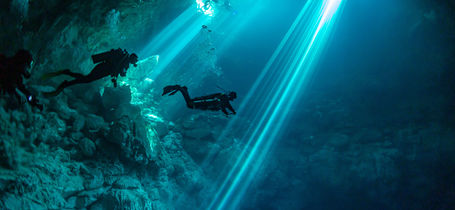Silhouette of three scuba divers in underwater Cenote in Yucatan, Mexico.