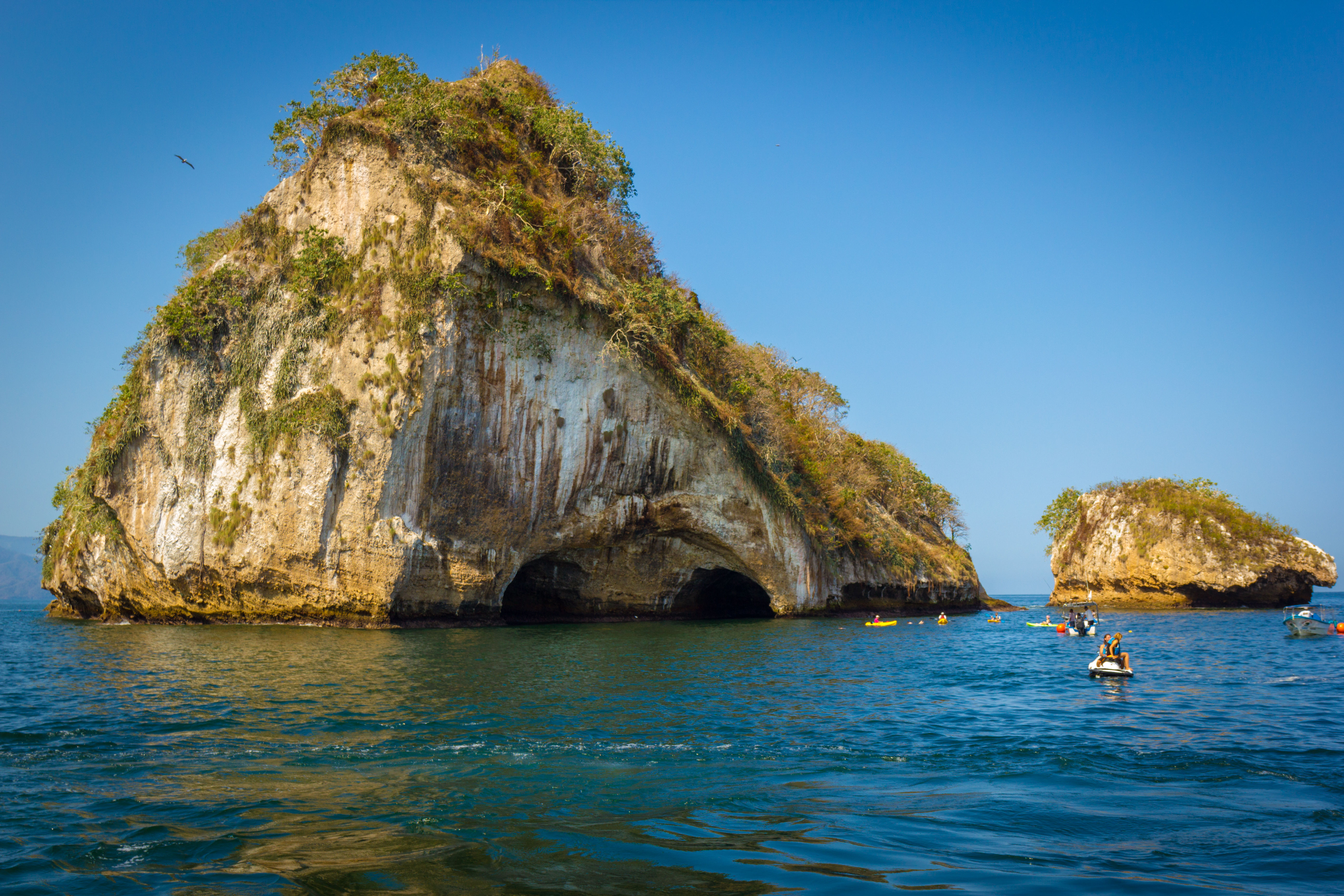 A big and small rock islands surrounded by blue water and kayakers in Jalisco, Mexico.