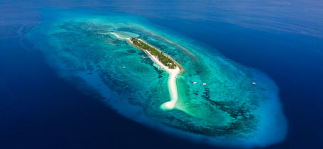 Aerial drone view of a beautiful tropical island with sandy beach surrounded by Coral Reef in Siquijor, Philippines.
