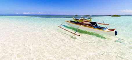 Traditional white fishing boat on crystal clear water over white sand and blue sky in Panglao, Philippines.