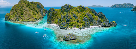 Aerial drone view of tropical Islands steep rocks and white sand beach in blue water El Nido, Mimaropa, Philippines.
