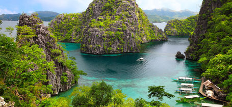 Landscape of view of Busuanga island with green rocky outcrops, blue waters and moored boats.