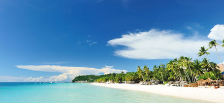 Beautiful pristine white beach with green trees and crystal clear turquoise water in Boracay, Philippines.