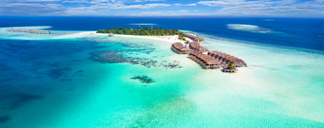 Aerial drone view of Maldivian island resort with white sand beaches and bungalows over turquoise waters in the Indian Ocean.