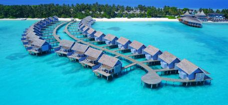 Aerial drone view of luxury water bungalow resort in the maldives.